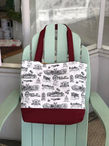 There is a tote bag hanging from the top of an adirondak chair. The tote is made of Toile of FSU fabric and has garnet accent fabric on the bottom and the straps.