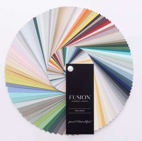 "Pictured is a Fusion Colour Fan Deck. It is a deck of rectangular cards in each Fusion Paint color with a cover in black with the words ""FUSION MINERAL PAINT FAN DECK paint it beautiful."" This fan deck is fully fanned out into a circle to show all of the colors."