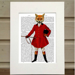A page from a book is framed with mat. Printed over the page is a figure wearing an old hunting outfit with a red coat. In their left hand is the crop and tucked under their right arm is their riding helmet. Instead of the head of a person they have the head of a fox. This image is a full body portrait of the fox figure.