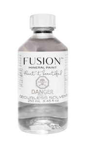 Pictured is a 250mL bottle of Fusion Odorless Solvent. It is in a clear bottle, showing the clear substence inside. It has a white Fusion label with a danger warning on it. The cap is also white.