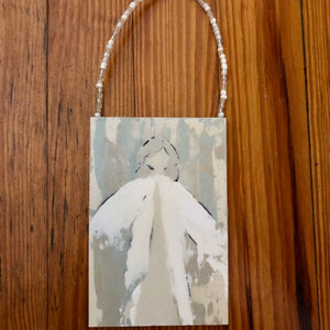Pictured is a rectangular door hanger or ornament. The handle has beads strung on it that are gold and white. On the hanger is an abstact painting of an angel. The angel wears white and tan. Her hair is a light gray. The background is brown, tan, and blue.