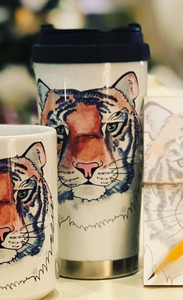 Pictured is a stainless steel travel mug. The background is white and it has a print of a watercolor painting of a tiger's face. The lid is black. The base is stainless steel.