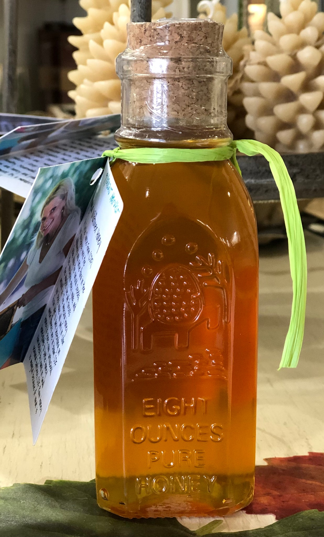 "Pictured is a glass bottle embossed with an image of a bee hive on a farm and the words ""EIGHT OUNCES PURE HONEY."" It is full of honey and capped with a cork."