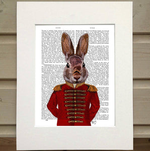 Pictured is a page from a book framed with mat. Printed over the top of the page is a figure in an old military coat. The coat is red with gold details. The figure has the head of a cute rabbit rather than the head of a person. The rabbit is pictured from the waist up and its arms are tucked behind its back.