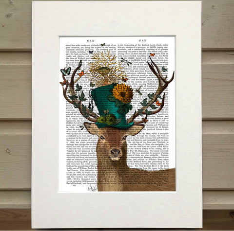 Pictured is a page out of a book framed with mat. Printed over the words on the page is the bust of a deer. The deer wears a blue top hat adorned with flowers. There are the branches of a tree coming out of the top of the hat with a birds nest in it. The antlers are covered in butterflies. There are birds and bugs howering around the hat and antlers.