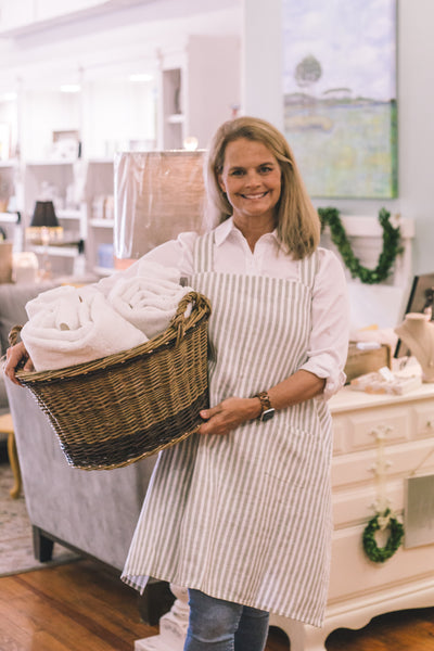 A smiling woman stands holding a willow woven laundry basket. She wears a crisp, white collared shirt with jeans and a striped apron. The laundry basket contains two rolled white towels.