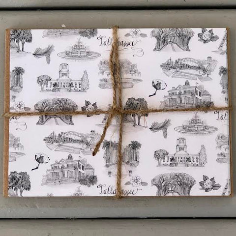 There is a stack of notecards with the black and whtie Toile of Tallahassee pattern on their covers and a stack of brown envelopes  tied together with twine.