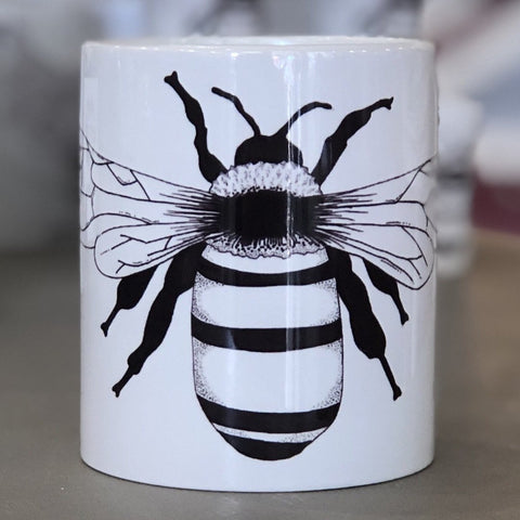 A small white mug with a bee design in the center of it.