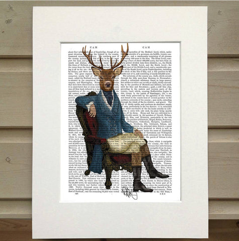 Pictured is a page from a book. Printed onto the page is a man lounging in a chair. He is dressed in old fashioned hunting clothes. He sits in an ornate chair. Instead of the head and face of a man, he has a deer head.