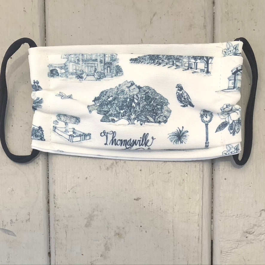 There is a blue and white Toile of Thomasville face mask with black elastic bands.