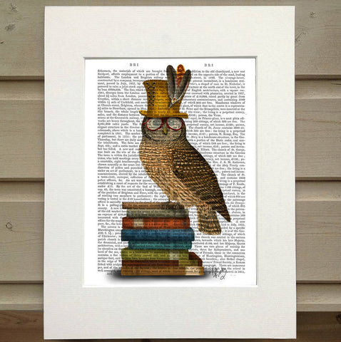 Pictured is a page from a book framed with mat. An opaque print of an owl is over the page. The owl is perched on a stack of books and it is wearing glasses and a gold feathered top hat.