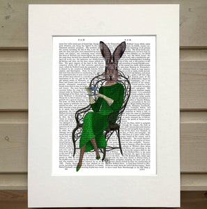 Pictured is a page from a book framed with mat. Printed over top the text on the book page is a figure sitting in a metal chair. The chair is organic in its style. The figure wears a quarter sleeve, full lenght green dress and a pair of matching pointed shoes. The figure holds a teacup and a small plate. Instead of the head of a person the figure has the head of a hare with its ears alert.
