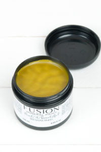 A container of Fusion Beeswax Finish is pictured from above. Its lid is off and you can see the wax finish inside. The finish is a yellow gold color and appears to have a smooth texture.