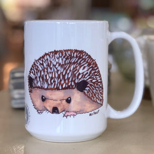 Pictured is a white coffe mug with a watercolor design of a hedgehog on it.