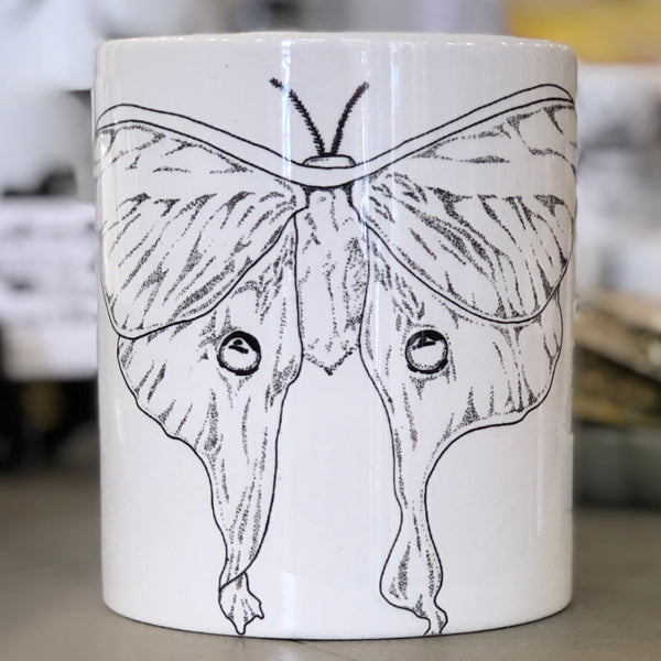 A large white mug with a black luna moth design in the center of it.