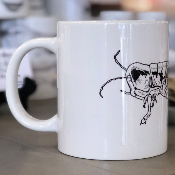 A large white mug with a black grasshopper design pictured from the side.