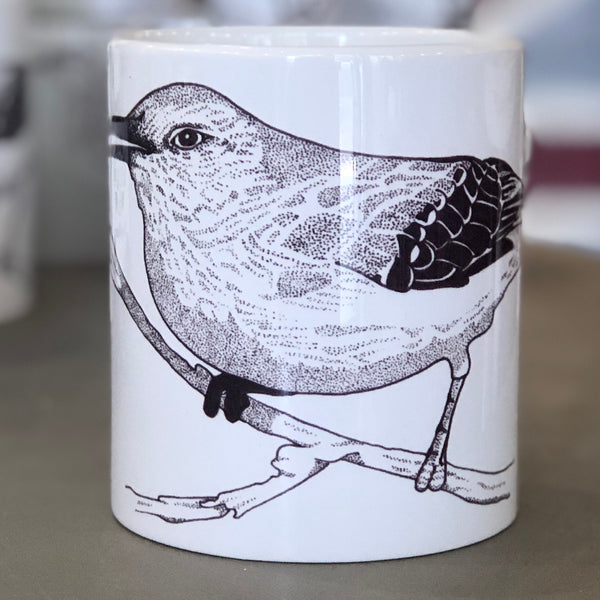 A large white mug with a bird design in the center of it. The bird is drawn in the style of pointillism.