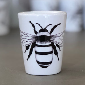 A shot glass is pictured. It has a pure white background with one black bee design in the center.