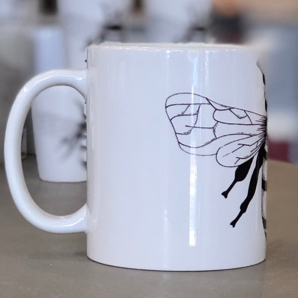 A large white mug with a black bee design pictured from the side.