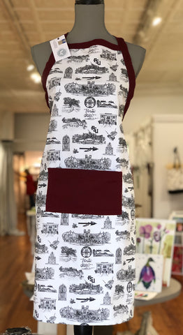 There is an apron on a mannequin. The apron is made with Toile of FSU fabric. There is a wide pocket on the front at about waist height and a trim around the top edge of the apron and both are made of garnet fabric.