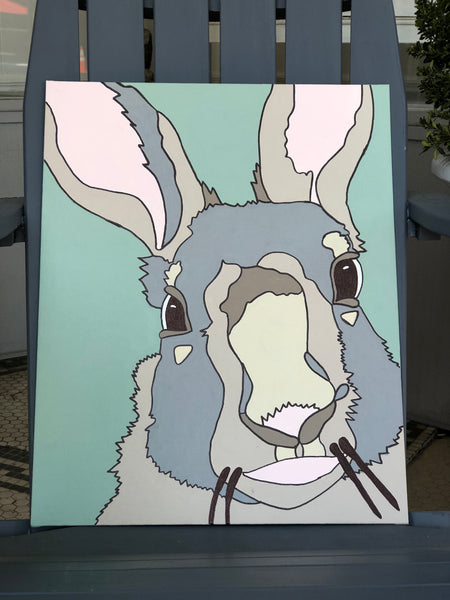 Pictured is a completed Paint-It-Yourself Canvas Kit of the hare design. It is propped up on an adirondak chair.