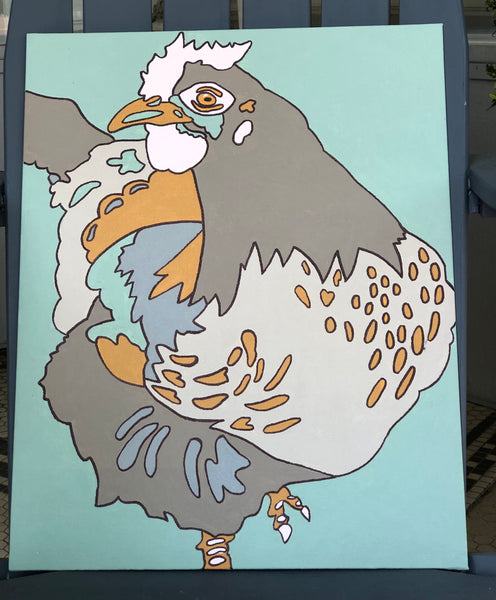Pictured is a completed Paint-It-Yourself Canvas Kit of the chicken design. It is propped up on an adirondak chair.