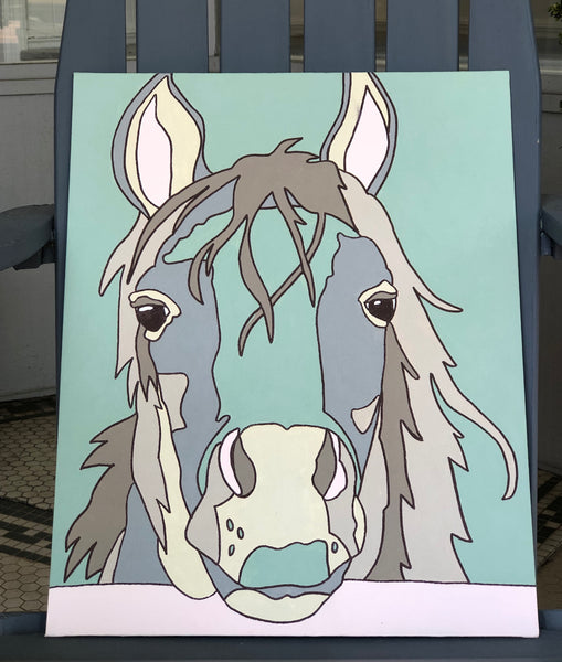 Pictured is a completed Paint-It-Yourself Canvas Kit of the horse design. It is propped up on an adirondak chair.