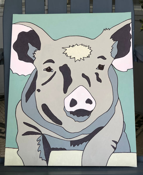 Pictured is a completed Paint-It-Yourself Canvas Kit of the pig design. It is propped up on an adirondak chair.