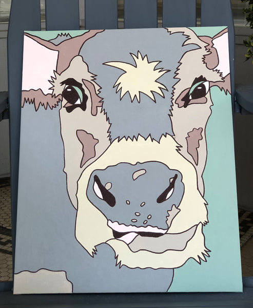 Pictured is a completed Paint-It-Yourself Canvas Kit of the cow design. It is propped up on an adirondak chair.
