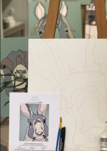 Pictured is an unpainted canvas kit for the hare. The canvas is propped up on an easel along with its paint color guide, two paintbrushes, and a black permanent marker. In the background are finish canvases of the goat and horse designs.