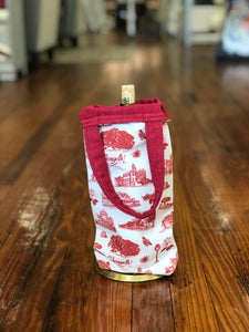 There is a red and white Toile of Thomasville wine tote with a wine bottle insid. The handles and the inner lining are made of red fabric.