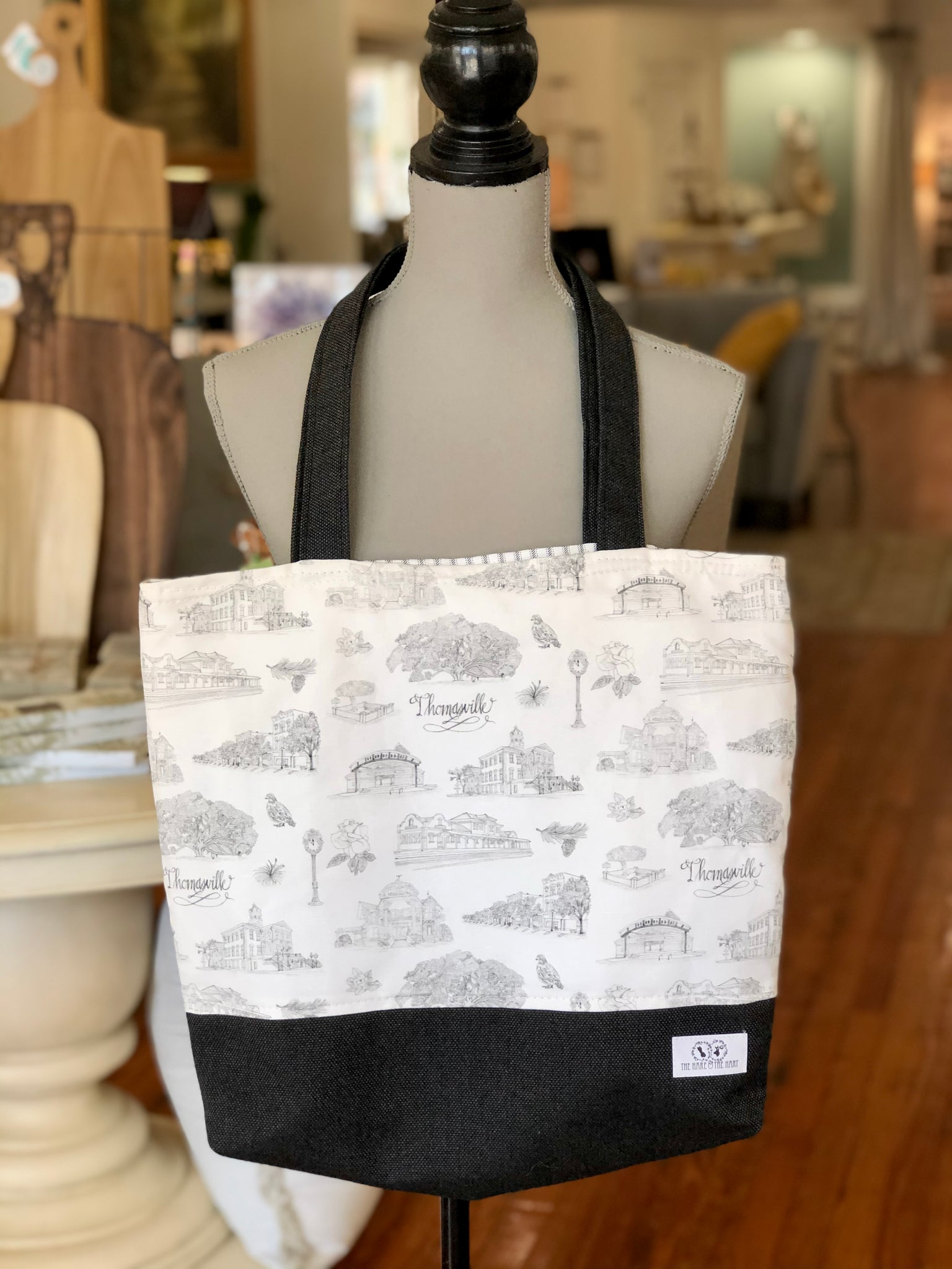 There is a black and white Toile of Thomasville tote bag hanging from the neck of a mannequin. The bottom of the bag and the handles are made of black fabric.