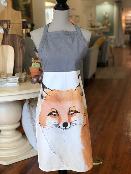 Pictured is an apron on a mannequin. From the waist portion down of the apron is white fabric with a print of a watercolor portrait of a fox. Above that portion of the apron it is made of blue fabric.