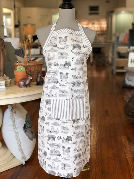 Pictured is an apron on a mannequin. The apron is made of black and white Toile of Tallahassee fabric in small print. There is a pocket in the center front of the apron and it is made of black and white ticking stripe fabric. The border of the top edge of the apron and the neck strap are also made of the black and white ticking stripe fabric.