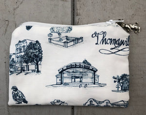There is a coin purse sized pouch in blue and white Toile of Thomasville fabric. The zipper pull is a metal rabbit standing on its hind legs.