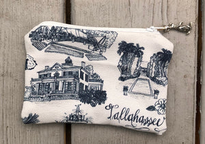 Pictured is a small fabric pouch which is about the size of a coin purse. It is made of blue and white Toile of Tallahassee fabric. It has a zipper closure and the zipper pull is a small metal rabbit standing on its hind legs.