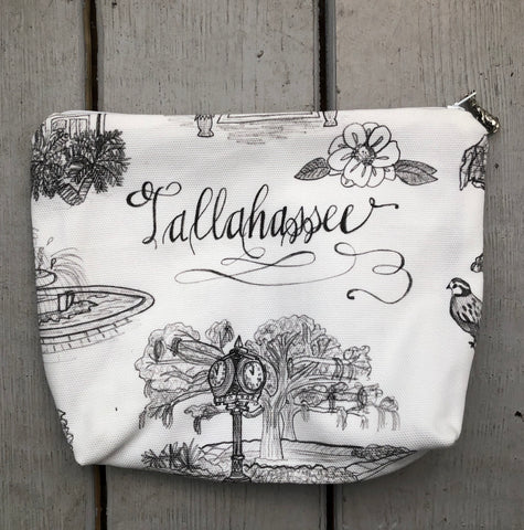 Pictured is a large fabric pouch with a zipper top. The zipper pull is a metal bunny standing on its hind legs. The fabric of the pouch is black and white Toile of Tallahassee fabric in large print.