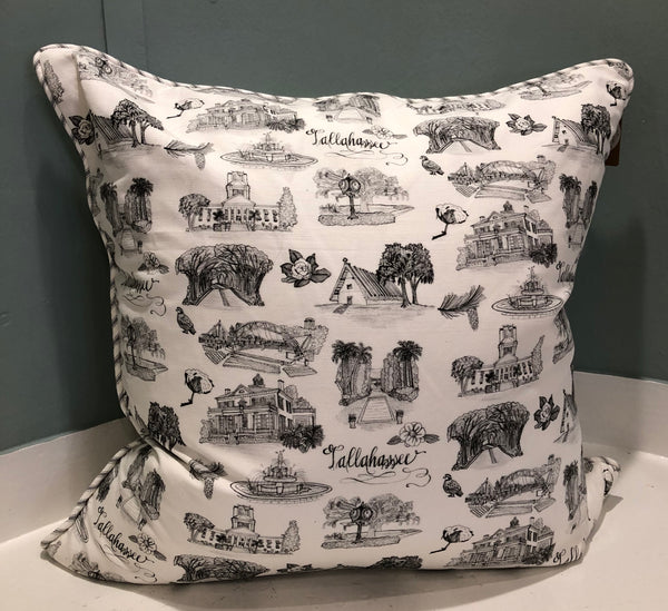 There is a square pillow covered with black and white Toile of Tallahassee patterned fabric. The edge of the pillow has black and white ticking stripe piping.