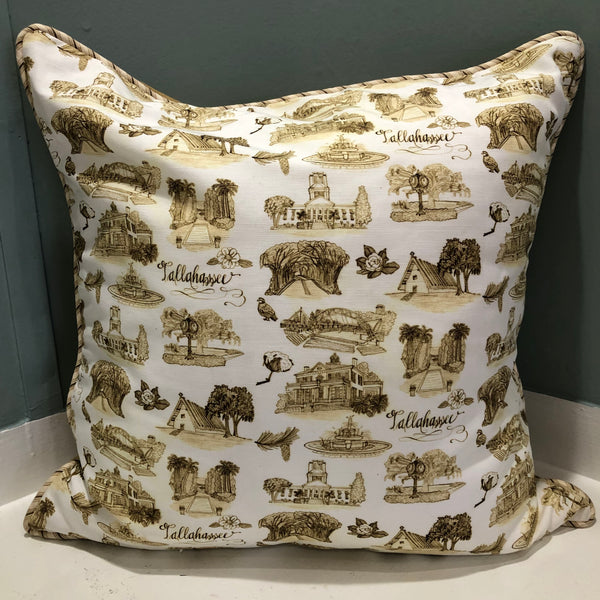 There is a square pillow covered with sepia and white Toile of Tallahassee patterned fabric. The edge of the pillow has sepia and white ticking stripe piping.