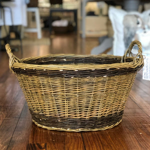 A willow woven basket in the shape of a laundry basket is pictured. It is wide and deep, and has two small handles on either end of it. It has a border of dark willow on the top and bottom edge, with a light willow in the middle and on the handles.