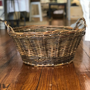 A round willow woven basket is pictured. It is all one color, with a band of slightly darker willow border the bottom edge. It has two handles on opposite ends of the basket.