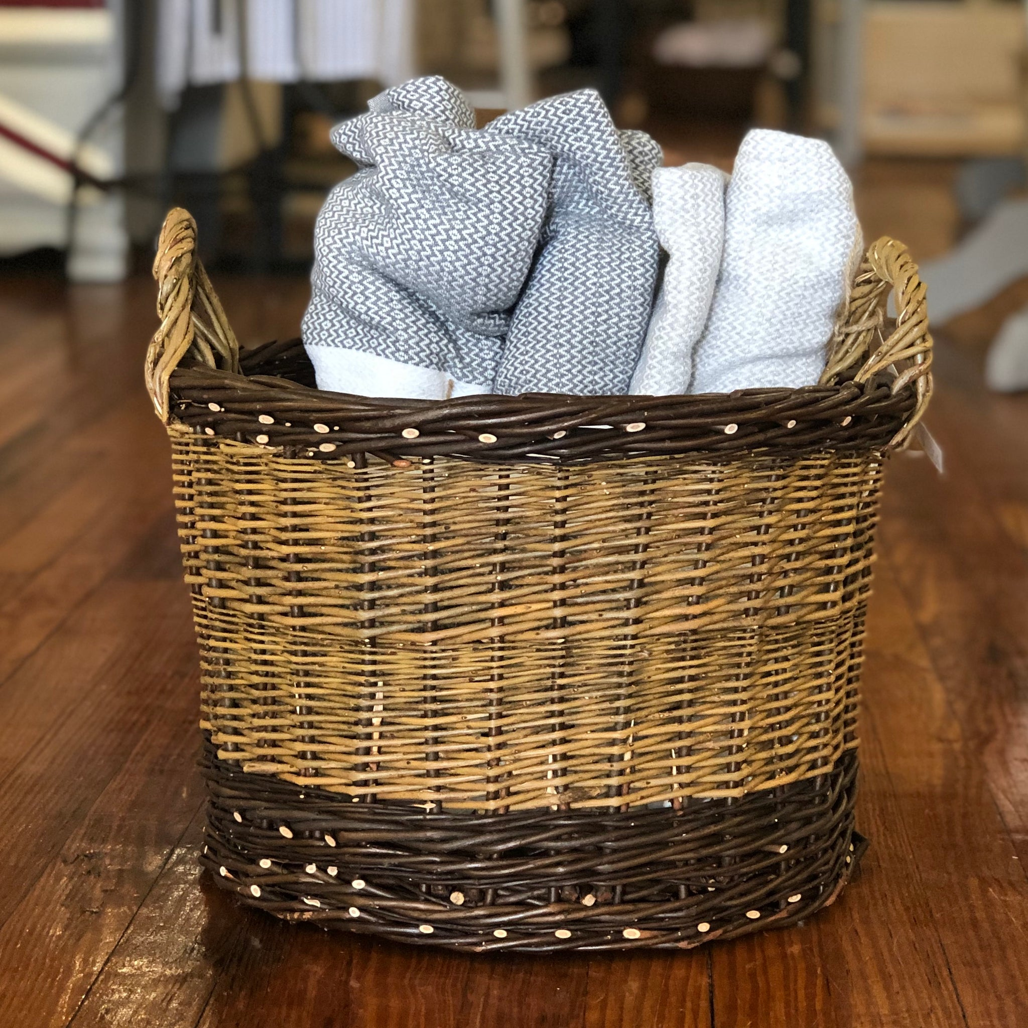 A small willow woven laundry basket is pictured. It is made of a light willow and has a dark willow border on both the top and bottom. The handles on either end of the basket are both made of light willow. The basket holds two folded gray blankets.