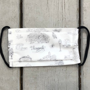 There is a fabric face mask made of black and white Toile of Thomasville fabric. The elastic ear bands are black.
