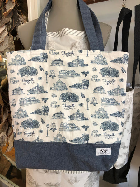 There is a Toile of Thomasville tote in blue and white fabric. The bottom and handles of the bag are blue fabric.