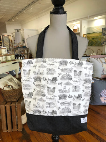 Pictured is a Toile of Tallahassee tote bag hanging from the neck of a mannequin. The tote is made of Toile of Tallahasse black and white fabric except for the base and handles of the bag, which are made of black fabric.