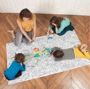 Pictured is a family sitting on the floor on top of an OMY XXL Coloring Poster Paris while they color it.