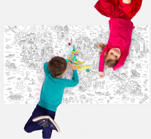Pictured are two kids laying on a floor covered with an OMY XXL Coloring Poster Atlas. The little boy is coloring and the little girl is laying on her back, looking up and smiling at the camera.
