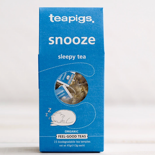 "Pictured is the packaging for Teapigs snooze tea. It is a rectangular blue box with an illustration of a sleeping cat on it. There is a circular clear plastic window through which the teabags can be seen. The label reads ""teapigs snooze sleepy tea organic feel-good teas."""