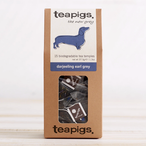 "PIctured is the packaging for Teapigs Darjeeling Earl Grey tea. It is a brown box with a clear plastic window in the front showing the teabags that are inside. The label on the box is white with a purple daschund. The label reads ""teapigs the new grey 15 biodegradable tea temples darjeeling earl grey."""