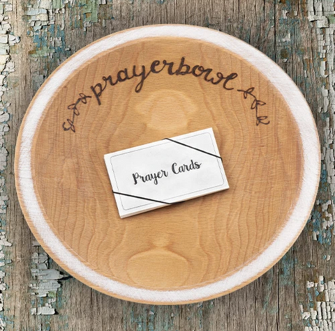 "Pictured is the Grace Prayer Bowl. It is carved out of wood and has a natural finish. The lip of the bowl is wide and painted white. Carved into the bowl along one edge, in cursive, is the words ""prayerbowl"" and two flower designs on either side. Inside the bowl is a stack of prayer cards."